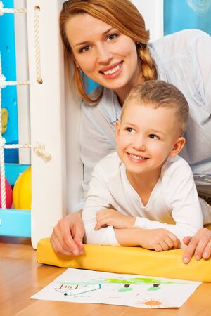 Happy mother and son smiling laying and drawing on the floor in the bedroom Stock Photo - 17421832