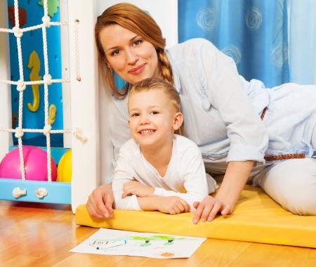 five years old: Felice genitori - madre e cinque anni figlio di posa e giocare insieme nella camera dei bambini