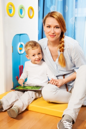 Mother and son sitting in bedroom and playing with new gadget Stock Photo - 17421898