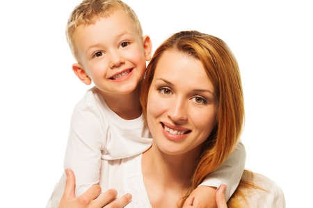Little blond five years old son hugs his smiling mother and both looking in camera photo