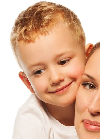Calm nice little boy smiling close to mothers face isolated on white photo