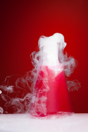 Science lab experiment with smoke coming from the flask photo