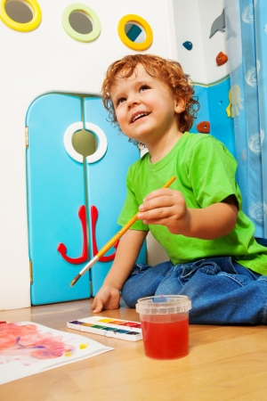 Two years old boy painting holding and dipping paintbrush into water bucket with smile on his face photo
