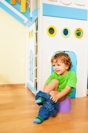 vasino: Piccolo di due anni ragazzo di mettere fuori i pantaloni mentre impara ad usare un vasino