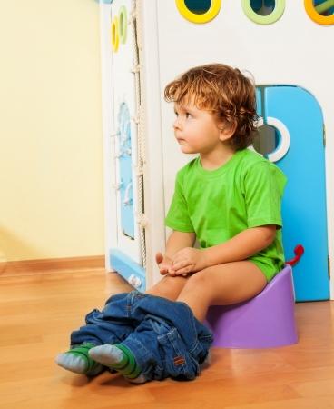 inodoro: Ni�o de dos a�os sentado en un orinal con sus pantalones Foto de archivo
