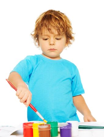 occupied: Occupied with painting with colors and holding paintbrush little boy painting