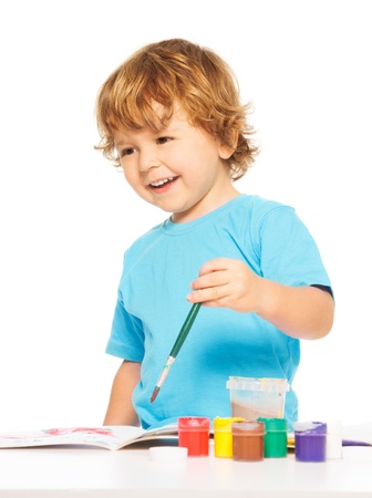 left handed: Happy smiling kid painting with paintbrush and smiling Stock Photo