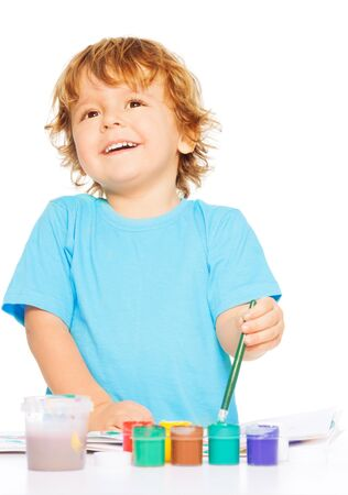 left handed: Happy smiling kid painting with paintbrush and colorful vivid colors, smiling, isolated on white