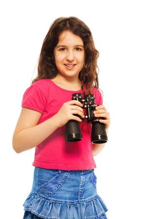 Buena chica que sostiene los prismáticos y sonriente, aislado en blanco Foto de archivo - 18256858