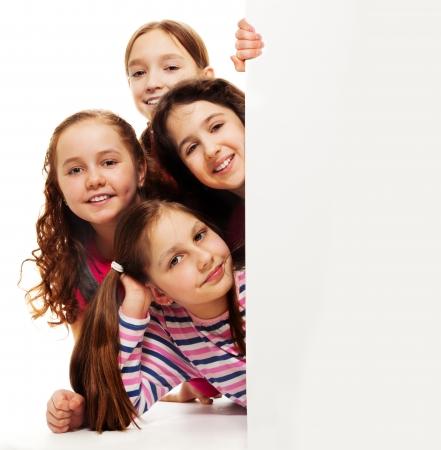 show bill: Grupo de muchachas felices tirado en el suelo y mirando detr�s de la publicidad insulsa cartelera Foto de archivo