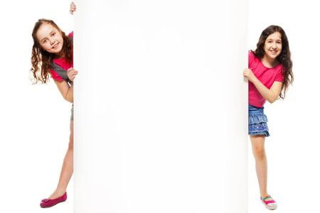 inserted: Two beautiful girls showing blank white poster for advertising to be inserted, standing isolated on white