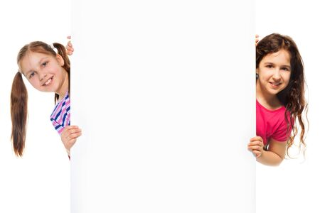 Two beautiful girls showing blank white poster for advertising to be inserted, isolated on white Stock Photo - 18255007
