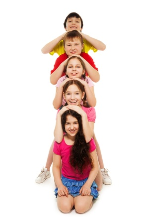 five years old: Group of kids laying their head on top of each others, smiling, Stock Photo
