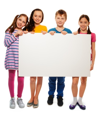 Group of school aged teen boys and girls, showing blank white placard board to write it on your own text isolated on white background photo
