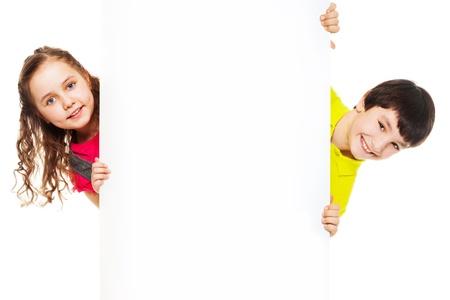 ni�os sosteniendo un cartel: Dos ni�os, ni�o y ni�a que muestra la tarjeta blanca en blanco para insertar mensajes publicitarios Foto de archivo