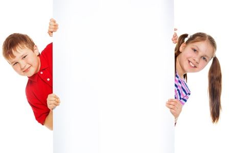 Two kids showing blank white board for advertising to be inserted Stock Photo - 18255044