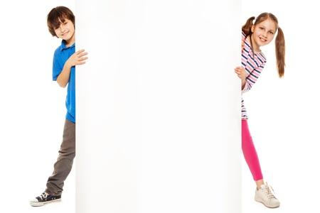 잘 생긴 소년과 광고를 삽입 할 빈 화이트 보드를 보여주는 아름다운 소녀