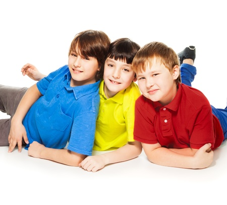 10 years old: Three cute boys laying together on the floor, happy and smiling, isolated on white Stock Photo