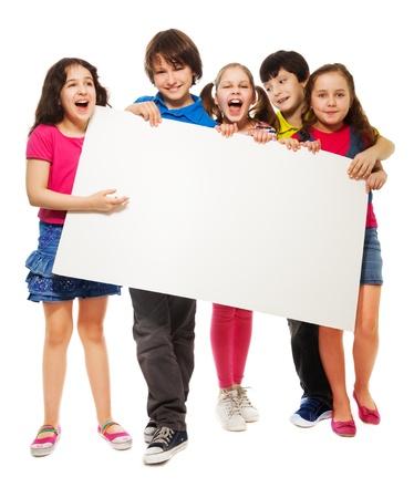 show bill: Feliz sonriente grupo de ni�os y ni�as, mostrando bordo cartel en blanco para escribir en su propio texto aislado en el fondo blanco
