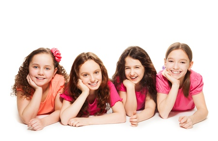 four person only: Four cute 10 years old girls in pink laying on the floor, smiling and look happy, isolated on white