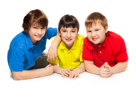 10 years old: Three schoolboys laying together on the floor, smiling, looks happy and exited, isolated on whtie