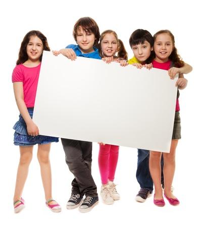 show bill: Grupo de edad escolar los chicos y chicas, que muestra tablero cartel en blanco para escribir en su propio texto aislado en el fondo blanco