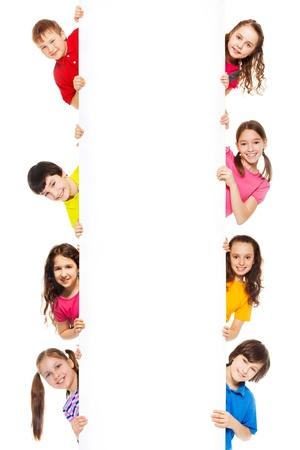 Sześć dzieci, chÅ'opcy i dziewczÄ™ta pokazano puste biaÅ'ej tablicy na reklamÄ™ powinny być wprowadzane, odizolowane na biaÅ'ym Zdjęcie Seryjne