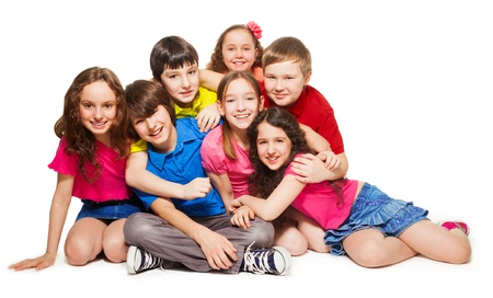 Group of 10 years old kids hugging, smiling, laughing, on white