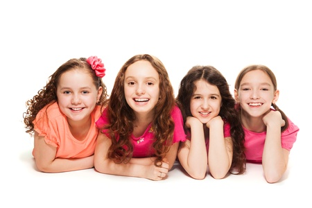 four person only: Four happy amazing 10 years old girls in pink laying on the floor, isolated on white Stock Photo