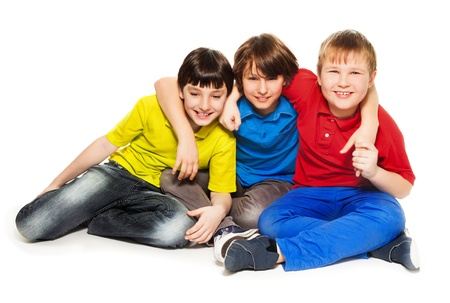 10 years old: Three boys friends sitting on the floor, hugging, smiling and look happy, isolated on white