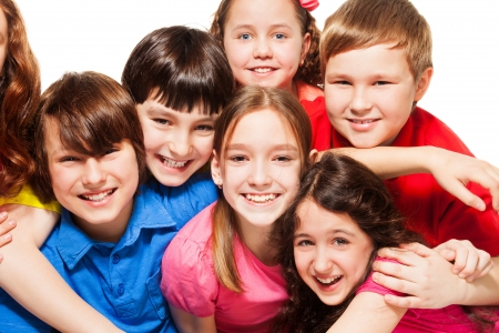 10 years old: Close-up of a group of 10 years old kids, boys and girls, hugging, smiling, laughing, on white