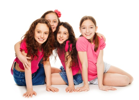 four person only: Four cute 10 years old girls in pink sitting, smiling and look happy, isolated on white
