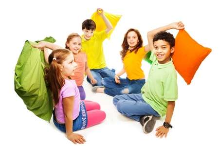 Happy five teen kids, Caucasian, black and Asian, boys and girls ready to start fighting with pillows, laughing and having fun, isolated on white photo