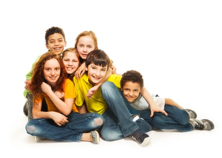 nine years old: Group of diversity looking kids, boys and girls sitting on the floor, in white background