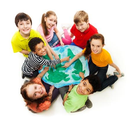 happy planet earth: Un grupo grande de la diversidad buscando chicos adolescentes, ni�os y ni�as que se�alan lugares donde se encuentran con el dedo de