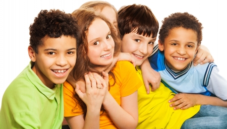 Group of happy diversity looking boys and girls smiling, laughing and hugging