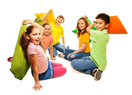 Happy five teen kids, Caucasian, black and Asian, boys and girls fighting with pillows, laughing and having fun, isolated on white photo