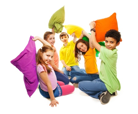 Happy five teen kids, diversity looking, boys and girls fighting with pillows, laughing and having fun, isolated on white photo