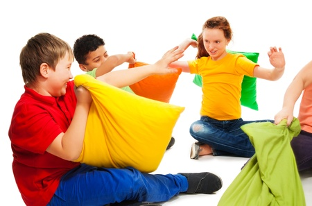 Happy three teen kids,  boys and girls ready to start fighting with pillows, laughing and having fun, isolated on white photo