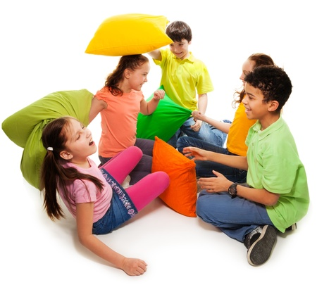 Five teen kids fighting with pillows, laughing and having fun, isolated on white photo