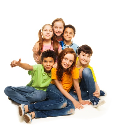 Positive happy group of kids sitting together, isolated on white