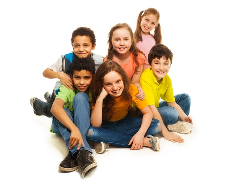 ethnic diversity: Group of black and Caucasian kids sitting happy together, smiling and laughing Stock Photo