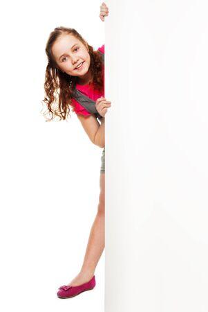 niños con pancarta: Longitud total bello retrato caucásica chica rizada con colas de caballo que oculta detrás de la pancarta blanca Foto de archivo