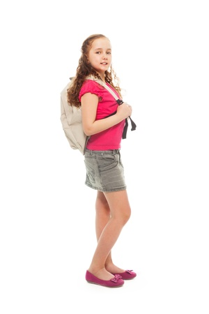 Portrait of happy, smiling, confident 9 years old girl with curly hair, wearing backpack isolated on white - full height portrait, side view photo