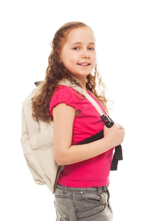 Portrait of happy, smiling, confident 9 years old girl with curly hair, wearing backpack isolated on white side view portrait Stock Photo - 18256582
