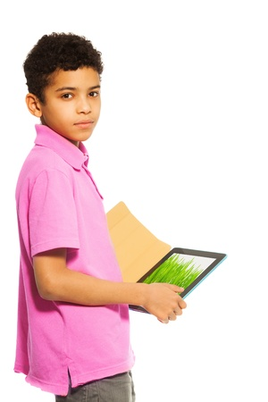 10 years old black boy standing with tablet pc, waist up portrait  (image on tablet from photographers portfolio) photo