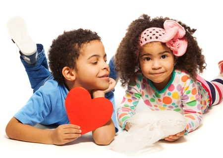frizzy: Black boy laying on the floor with little girl with frizzy hair holding red heart made of paper