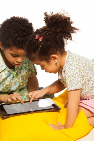 three children: Black boy and girl playing with digital tablet computer and looks very busy