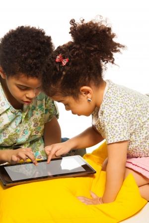 ni�os sentados: Muchacho negro y muchacha que juega con el ordenador tableta digital y se ve muy ocupado