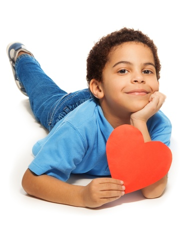 Cute five years old boy with heart symbol laying isolated on white